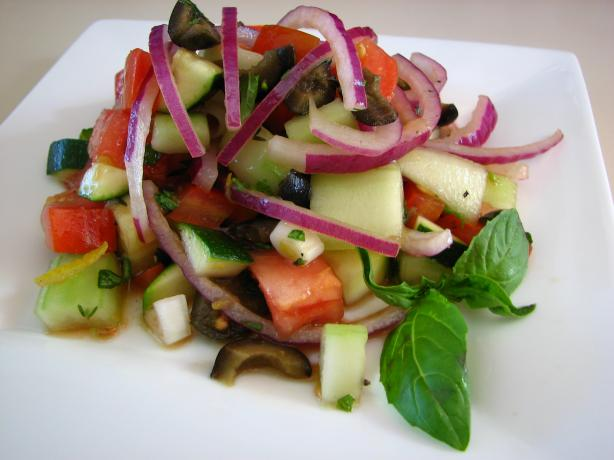 Cucumber Tomato Salad With Zucchini and Black Olives and a Lemon. Photo by Dannyz